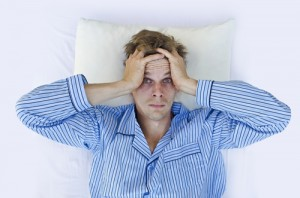 Man having trouble sleeping, eyes wide in bed
